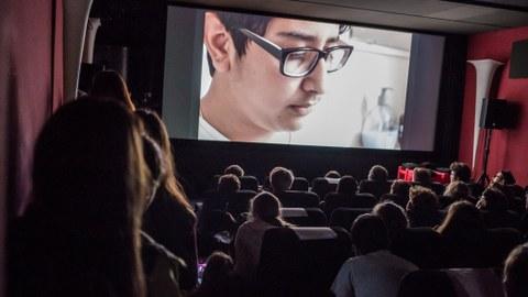 Blick in einen dunklen Kinosaal, auf der Leinwand ist ein junger Mann mit Brille zu sehen.