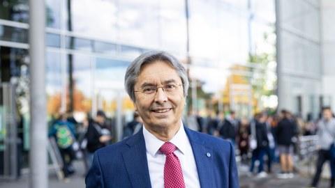 Prof. Müller-Steinhagen steht im blauen Anzug und roter Krawatte vor dem Hörsaalzentrum, Studenten sind im Hintergrund