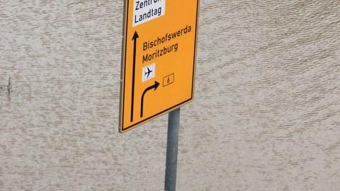 Ein Straßenschild/Wegweiser steht in einer Wassermasse.