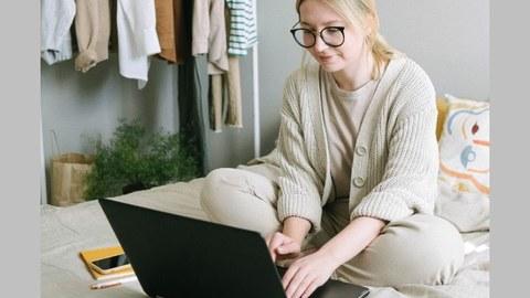 Eine junge, blonde Frau mit Zopf und Brille sitzt auf einem Bett und schaut in den aufgeklappten Laptop.