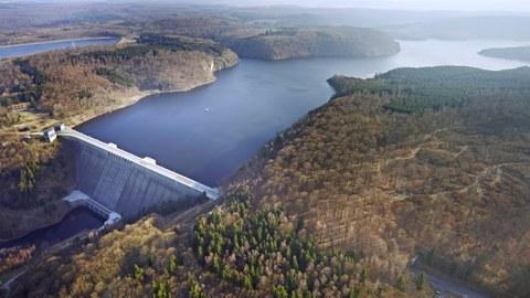 Foto einer Talsperre mit bewaldeten Ufern.
