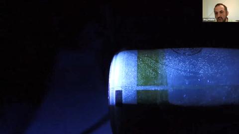 Auf schwarzem Hintergrund ist oben rechts ein kleines Foto des Referenten zu sehen, darunter größer eine blaue Flasche, auf der man Fingerabdrücke sieht.
