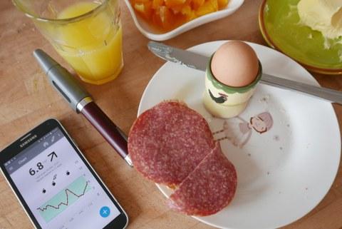 Auf einem weißen Frühstücksteller befinden ein Ei im Eierbecher und ein Salamibrot. Links daneben liegen ein Kuli und ein Smartphone, auf dem ein Diagramm zu sehen ist.