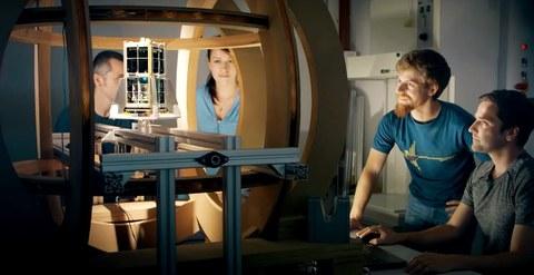 Drei Männer und eine Frau stehen halbkreisförmig um einen Weltraum-Versuchsaufbau