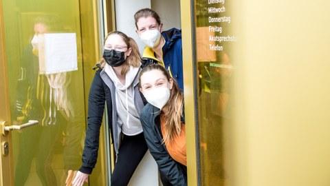 Drei junge Frauen mit Mundschutz schauen aus einer geöffneten gelben Glastür.