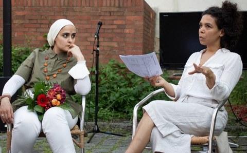 Links sitzt eine Frau mit weißem Kopftuch, einen Blumenstrauß auf dem Schoß, rechts eine Frau im weißen Kleid, sie spricht und hält einen Bogen Papier in der Hand. Im Hintergrund eine Backsteinwand und eine Hecke, davor ein Mikrophon.