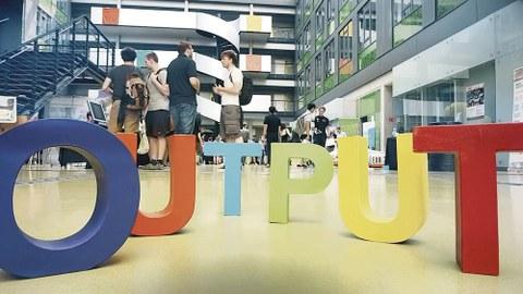"""Im Foyer des Informatik-Baus steht in bunten Buchstaben """"Output"""". Dahinter stehen vier junge Männer."""