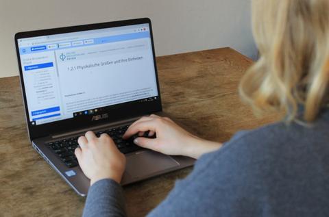 Schräge Rückenansicht einer blonden Frau, die am Laptop arbeitet.