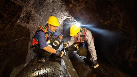 Zwei Männer mit gelben Bauhelmen untersuhchen knieend Wasser in einem Kanal