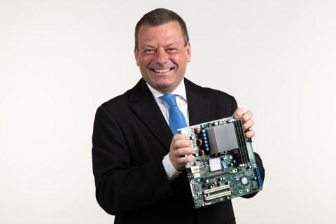 Porträtfoto Professor Lehner, er hält ein elektronisches Bauteil in der Hand.