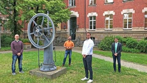 Vier Männer stehen verteilt im Innenhof eines Backsteinbaus, sie umringen ein historisches Modell einer Maschine
