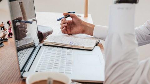 Ein junger Mann sitzt am Laptop und arbeitet allein, ein Gesicht ist nicht zu erkennen.