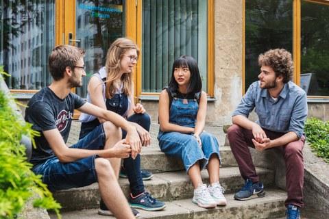 Auf dem Foto sitzen Studenten verschiedener Nationaliäten auf einer Treppe im Freien und unterhalten sich.