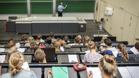Blick von hinten/oben in eine Vorlesung, vorn steht der Professor und schreibt an eine Tafel.