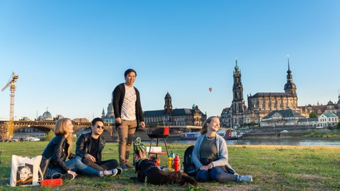 Eine Gruppe junger Menschen sitzt auf der Elbwiese, im Hintergrund die Dresdner Kulisse mit Hofkirche.