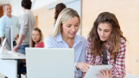 Eine Frau erklärt einer sehr jungen Frau etwas an einem Tablett, vor ihnen steht ein Laptop. Im linken Hintergrund sind vier weitere Personen stehend an einem Pult zu sehen.