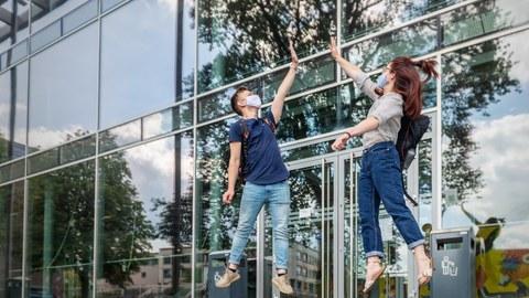 Ein Student und eine Studentin springen vor dem Hörsaalzentrum ein wenig in die Höhe.