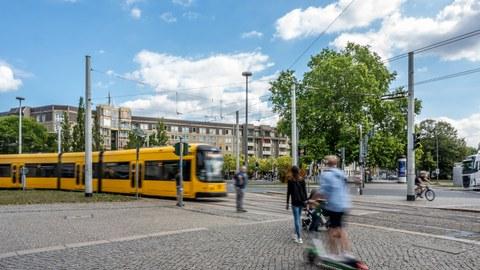 Foto eines großen Platzes, links fährt eine Straßenbahn ins Bild, im rechten Vordergrund sind Passanten zu sehen.