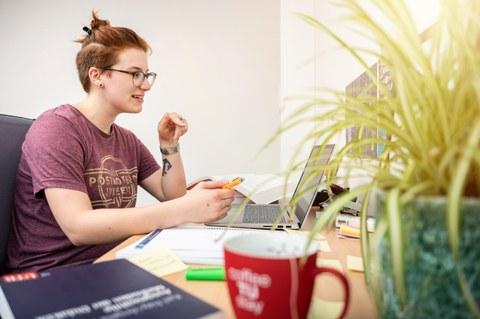 Eine Frau sitzt an einem Schreibtisch, auf dem sich ein Laptop und auch Bücher befinden.
