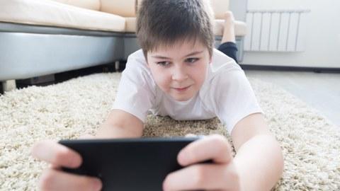 Ein Junge liegt mit dem Kopf nach vorn auf einem hellen Teppich und schaut auf sein Handy