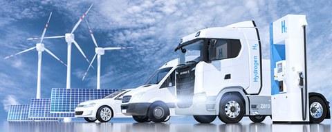 Weiße Autos vor hellblauem HImmel v.l. ein PKW, ein Kleinbus und ein LKW inmitten von Solarpaneelen, Windrädern und Elektro-Tanksäule