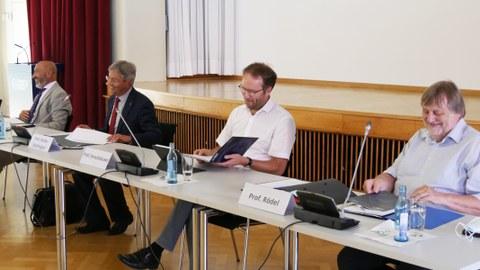 An einem langen Tisch sitzen der Rektor und seine drei Prorektoren.