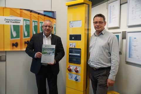 Zwei Herren stehen im Bild, der linke hält eine Urkunde in der Hand. Dazwischen steht ein gelber, übermannsgroßer Automat