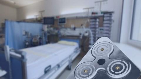Blick in ein Intensivzimmer, im Vordergrund rechts unten eine dreieckige, drahtlose EKG-Elektrode.