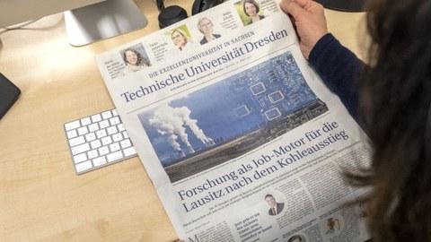 Vor einer hellen Tischplatte hält eine Person eine Zeitungsseite ins Bild.