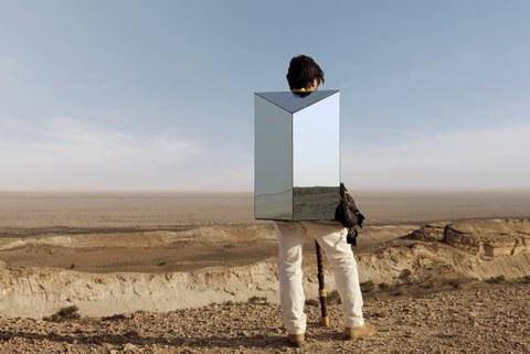 Ein junger Mann in heller Hose steht mit dem Rücken zu uns vor einer hellbraunen, verbrannten Landschaft, der Himmel ist leicht bewölkt. Auf dem Rücken trägt er eine geometrische Spiegelfigur