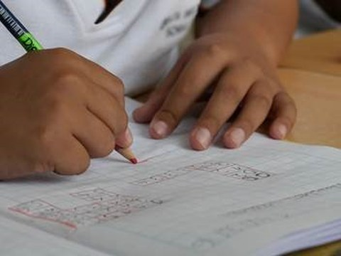 Zwei Kinderhände, es wird mit einem Bleistift in ein Heft geschrieben.