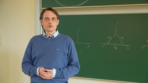 Professor Dominik Stöckinger vor einer mit Formeln beschriebenen, grünen Tafel.