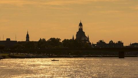 Silhouette der Stadt Dresden von der Elbe aus gesehen im Abendlicht.