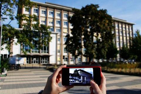 Im Hintergrund der aktuelle Andreas-Schubert-Bau. Im Vordergrund sieht man das historische Gebäude auf einem Smartphone.
