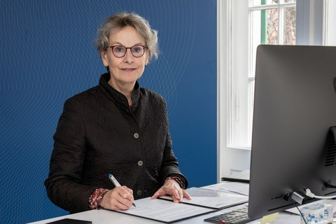 Frau Professorin Staudinger sitzt vor einer blauen Wand, vor sich eine aufgeschlagene Mappe und einen Laptop.