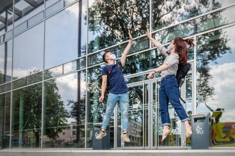 Ein junger Mann und eine junge Frau springen vor dem Hörsaalzentrum nach oben und klatschen dabei mit jeweils der rechten Hand aneinander