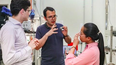 Zwei Männer und eine Frau (rechts) stehen in einem Labor und unterhalten sich.