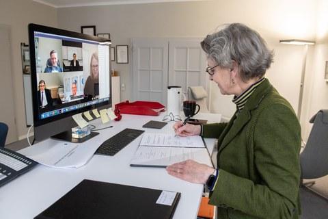 Die Rektorin der TUD sitzt im rechten Bildrand am Schreibtisch und unterzeichnet ein Schriftstück, im Bildschirm gegenüber sind die Teilnehmer der Videokonferenz zu sehen.
