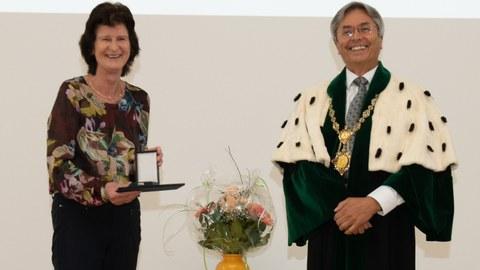 Frau Dr. Stange steht links im Bild, sie hält die Ehrenmedaille in der Hand. Der Rektor steht im Talar rechts. Beide lachen.