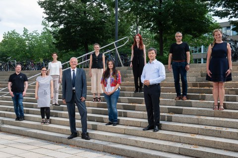 Schräger Blick auf eine Treppe im Freien, auf der Treppe stehen verteilt 10 Personen mit Blick in die Kamera.
