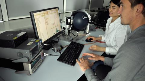 Auf der linken Seite sitzen hintereinander eine junge Frau und ein junger Mann. Beide blicken auf einen aufgeklappten Laptop.