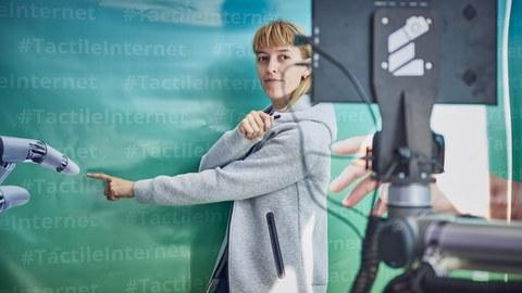 eine junge Frau steht vor einer Wand in blau-grün mit dem mehrfachen Schriftzug #TactileInternet steht und zeigt mit dem Zeigefinger nach vorn.