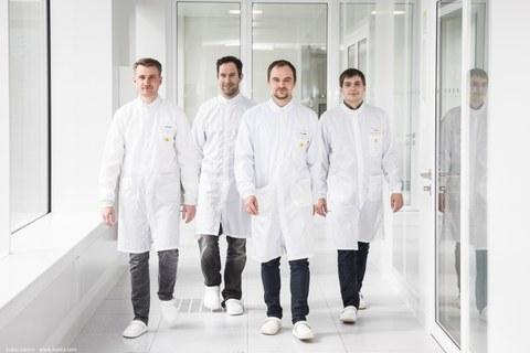 Vier Männer in weißen Kitteln laufen einen weißen Gang entlang der Kamera entgegen.