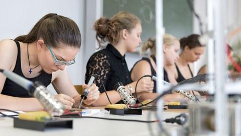 Vier junge Frauen sitzen an einem langen Tisch und arbeiten mit Lötkolben an einem Werkstück.