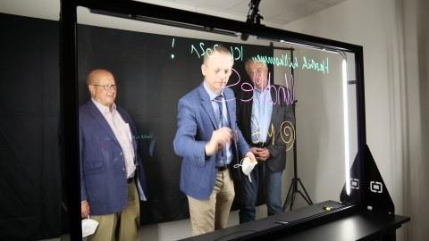 Drei Herren stehen hinter einem durchsichtigen Lightboard, der Herr in der Mitte beschriftet das Board.