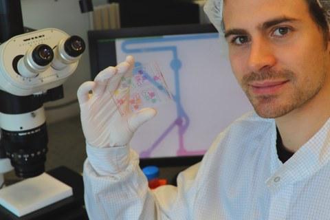 Doktorand Anthony Beck, Mit-Entwickler der Technologie, hält einen chemischen Schaltkreis mit gefärbten Analysemedien. Auf dem Monitor im Hintergrund ist ein Mikroskopiebild eines der chemischen Transistoren des chemischen ICs zu sehen.