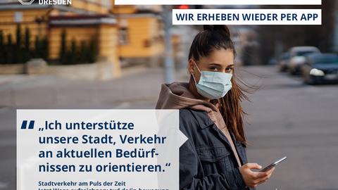 Eine junge Frau mit Maske bedient ihr Handy