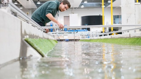Im Vordergrund ein Wasserkanal in einer Versuchshalle. Im Hintergrund arbeitet ein junger Mann mit Brille an einem Versuchsaufbau im Wasser.
