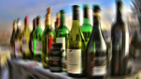 Ein Tisch voll Alkohol-Flaschen, das Bild erscheint verschwommen