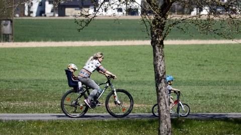 Eine Junge Frau fährt Mountainbike, im Kindersitz hinter ihr sitzt ein Kleinkind, ein weiteres Kind fährt auf seinem Fahrrad vor ihr.